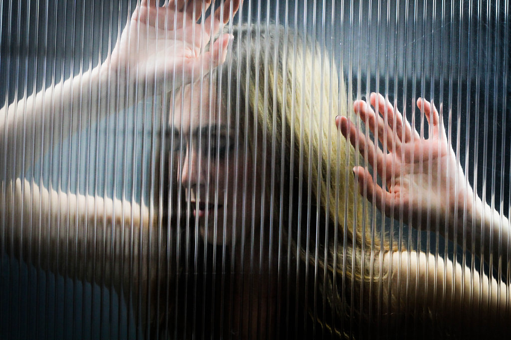 young woman photographed through glass, she rises her hand