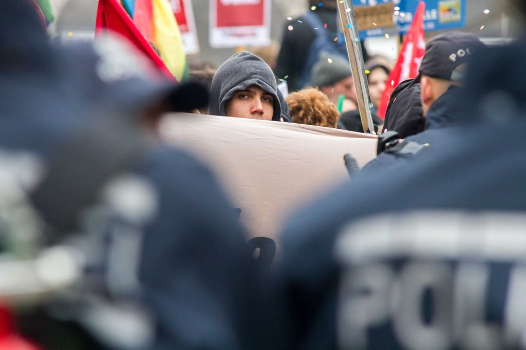 reportage of street demonstration in Stuttgartortrait of young man hidden behind a flag